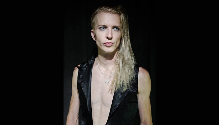 Fetish House Apprentice Kai androgynous man with high chiselled cheek bones and long blonde hair wearing a vest that shows his defined chest