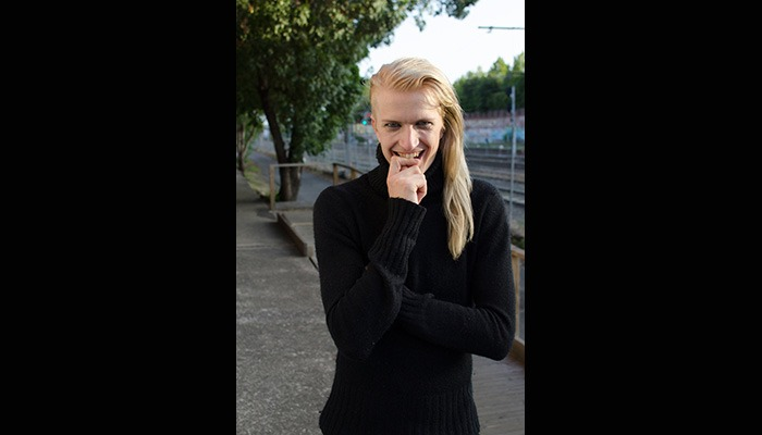 Fetish House Apprentice Kai with long blonde hair wearing a high neck black jumper standing outdoors