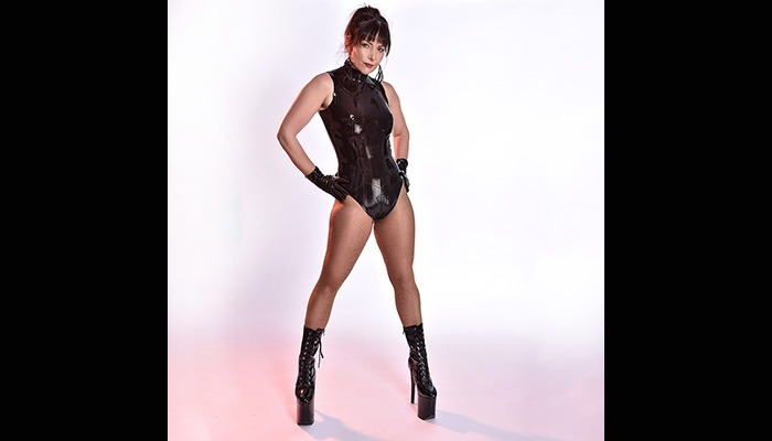 Fetish House Mistress Alex Vicia wearing a see through latex body suit and ankle boots standing with hands on her hips