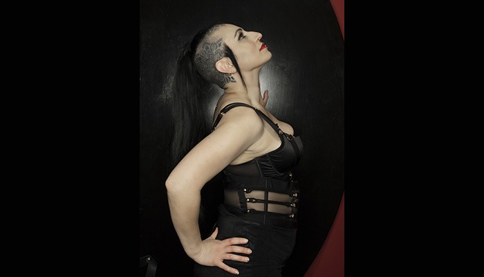Mistress Asha from the side looking up showing head tattoo with red lipstick and long pony tail