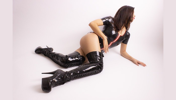 Fetish House Mistress Misty laying down with thigh high black shiny high heel boots and black latex dress