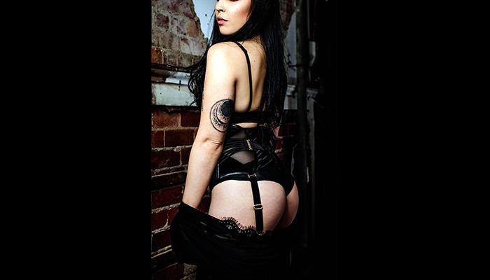 Mistress Raven Mercury in black suspenders standing against a red brick wall